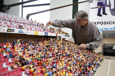 Javier Grela, director del proyecto, colocando Playmobils en las gradas del estadio el Molinón en la sierra del Trabanquín