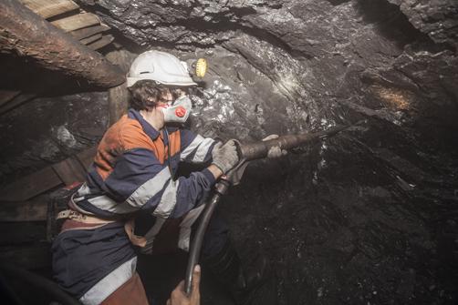 Una visitante picando carbón en el interior del Pozo Sotón