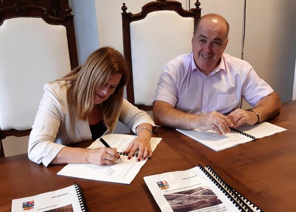 La alcaldesa de Langreo, Carmen Arbesú, y el alcalde de San Martín del Rey Aurelio, José Ángel Álvarez durante la firma del convenio.