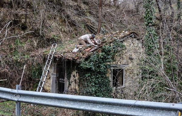 Trabajos de reparación en el tejado del molino del Carneru en Bueres (Caso).